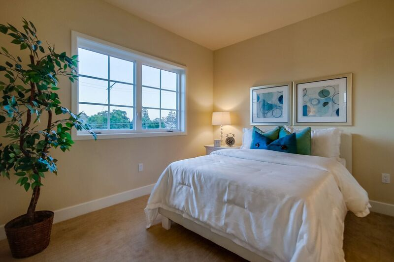 Bedroom staging with white, green and blue accents