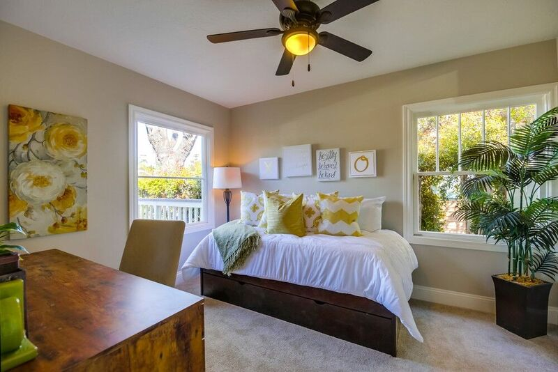 Bedroom staging with white and yellow accents