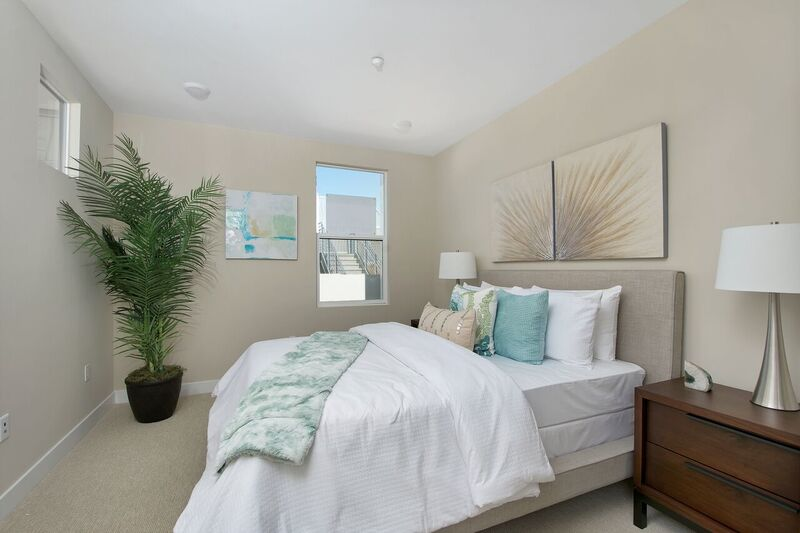 Bedroom staging with white, beige and blue